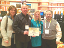 (left to right) Kidz Gear's Laurie Peterson & Jack Peterson, with Karen Thomas, Thomas PR and Rick Doherty, Envisioneering Showing Off Kidz Gear's Envisioneering Innovation & Design Award at Showstoppers.
